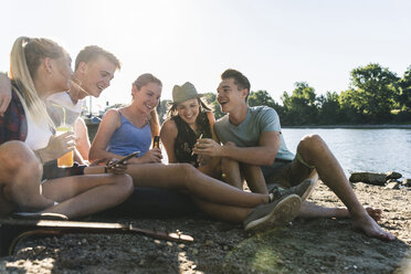 Group of happy friends sitting at the riverside with drinks and cell phone - UUF14903