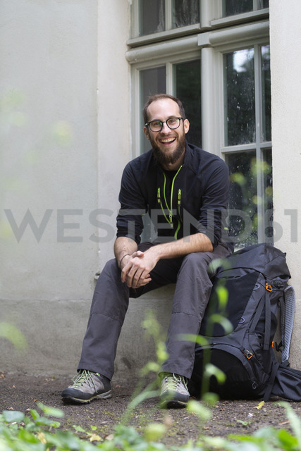 Portrait of laughing man with backpack waiting outdoors - NGF00469