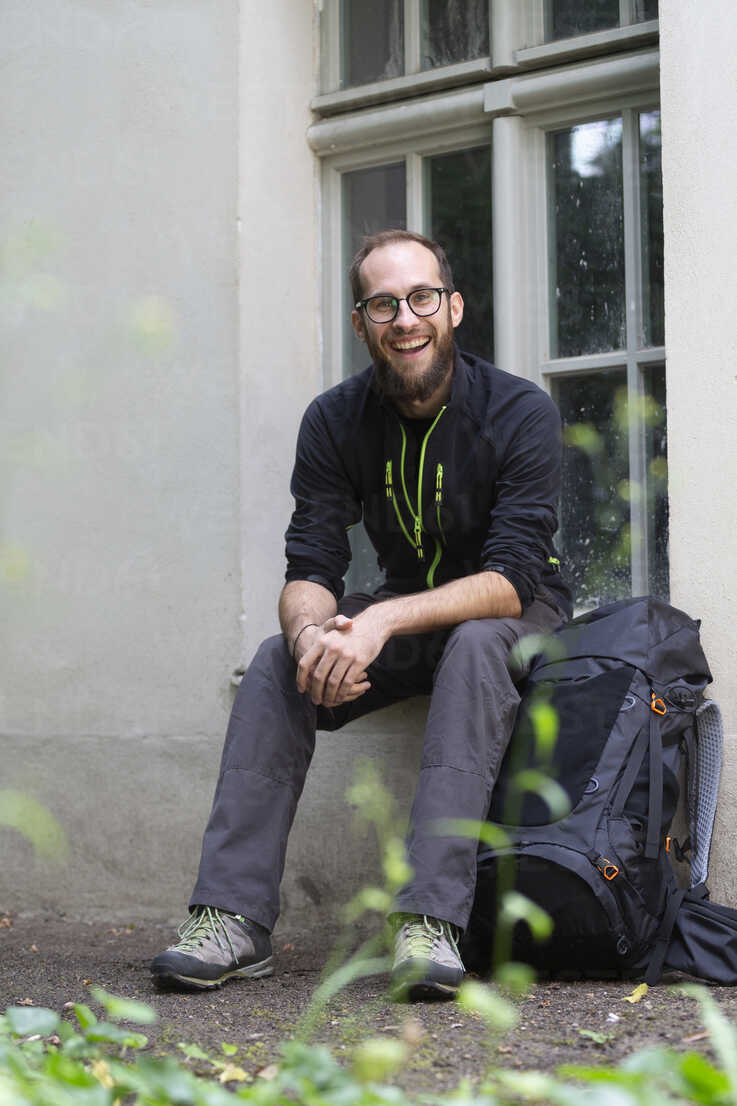 Portrait of laughing man with backpack waiting outdoors - NGF00469 - Nadine Ginzel/Westend61
