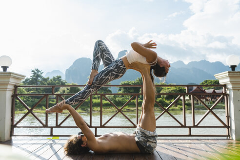 Laos, Vang Vieng, Young couple doing acro-yoga on a terrace - AFVF01219