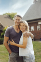 Portrait of smiling mature couple embracing in garden of their home - JOSF02445