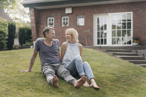 Happy mature couple sitting in garden of their home - JOSF02448