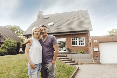 Portrait of smiling mature couple standing in front of their home - JOSF02451