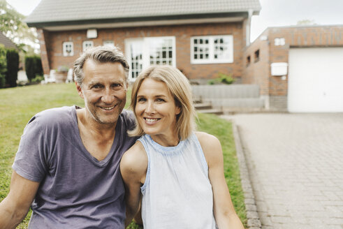 Portrait of smiling mature couple sitting in garden of their home - JOSF02454