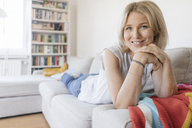 Portrait of smiling mature woman lying on couch at home - JOSF02457