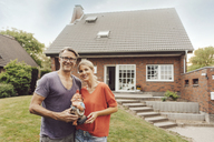 Portrait of smiling mature couple standing in front of their home holding garden gnome - JOSF02460
