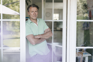 Portrait of serious mature man standing at French window - JOSF02463