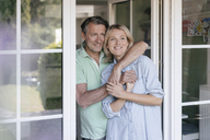 Happy mature couple hugging at French window - JOSF02466
