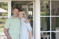 Portrait of smiling mature couple at French window - JOSF02469