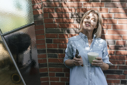 Relaxed mature woman leaning at house wall holding cup and pruner - JOSF02475