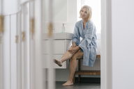 Portrait of smiling mature woman sitting in bathroom touching her legs - JOSF02478