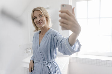 Smiling mature woman taking a selfie in bathroom - JOSF02487