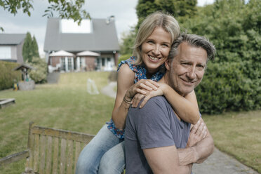 Portrait of smiling mature couple embracing in garden of their home - JOSF02502