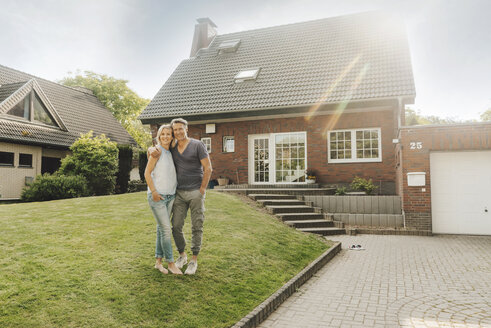 Smiling mature couple embracing in garden of their home - JOSF02505