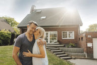 Portrait of smiling mature couple embracing in garden of their home - JOSF02508