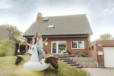 Happy mature couple with inflatable pool toy in garden of their home - JOSF02511