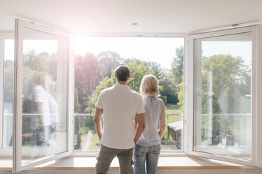 Mature couple looking out of window into the sun - JOSF02514