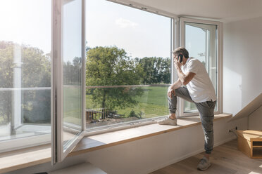 Mature man on the phone at the window in empty room - JOSF02517