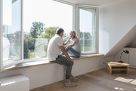 Mature couple with cell phone sitting at the window in empty room - JOSF02520