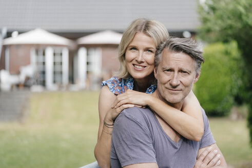 Portrait of smiling mature couple embracing in garden of their home - JOSF02523