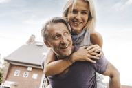 Happy mature couple in front of their home - JOSF02526