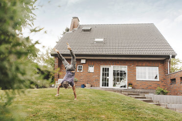 Mature man doing a handstand in garden of his home - JOSF02529