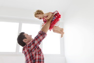 Man wearing checked shirt throwing young girl in the air. - MINF04565