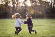 Two young girls, twin sisters, holding hands, playing on a lawn. - MINF04589