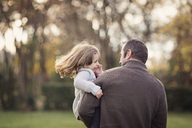 Man standing outdoors, holding smiling young girl with brown hair. - MINF04592