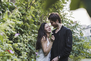 Happy young couple standing in shrubbery - AFVF01235