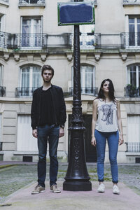 France, Paris, young couple standing at lamp post in front of urban building - AFVF01238