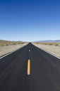 A black top road with a central line reaching into the distance, the road ahead. - MINF04756