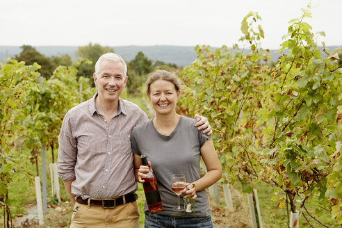 A couple, vineyard founder and her partner standing among the rows of vines. - MINF04861