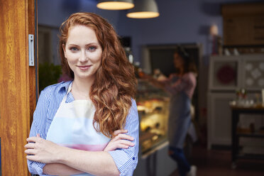 Portrait of smiling young woman at the entrance of a bakery - ABIF00802
