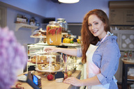 Portrait of smiling young woman working in a cafe - ABIF00805