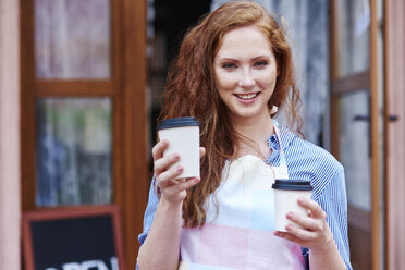 Portrait of smiling waitress holding two cups of coffee - ABIF00817