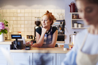 Smiling young woman at the counter in a cafe looking sideways - ABIF00829