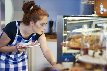 Young woman working in a cafe looking at cakestand - ABIF00832