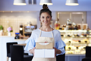 Portrait of smiling young woman holding cake boxes in a cafe - ABIF00835