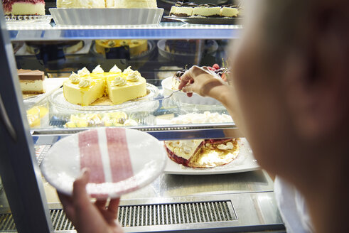 Woman working in a cafe serving a piece of cake - ABIF00841