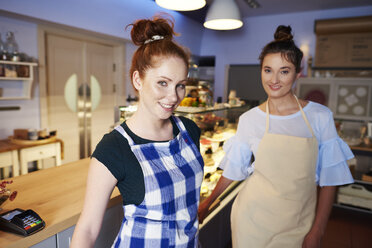 Portrait of two smiling women at the counter in a cafe - ABIF00844