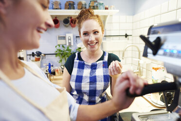 Two female baristas at work in a cafe - ABIF00847