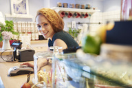 Portrait of smiling young woman with card reader at the counter in a cafe - ABIF00856