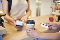 Close-up of customer paying by credit card in a cafe - ABIF00859