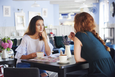 Two women talking and drinking coffee at cafe - ABIF00862