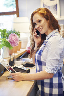 Smiling young woman working in a cafe talking on cell phone - ABIF00868