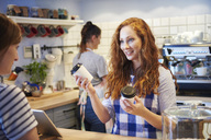 Waitress talking to customer at counter in a cafe - ABIF00874