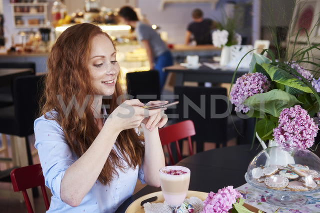 Smiling young woman taking cell phone picture of a drink in a cafe - ABIF00877
