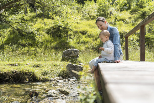 Mother and daughter sitting on wooden bridge, mountain stream - DIGF04725