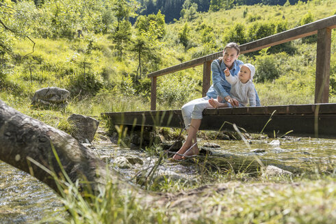 Mother and daughter sitting on wooden bridge, mountain stream - DIGF04728